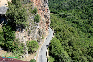 Chateaudouble, road with a cyclist down the gorges